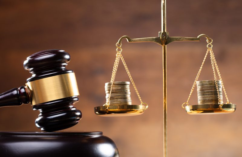 Close-up Of Wooden Gavel And Stacked Coins On Golden Justice Scale