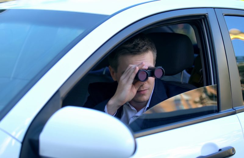 Man in suit spying from car using binoculars, private detective investigation